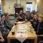 Photograph of young people and the Vicar playing Monopoly at a kitchen table